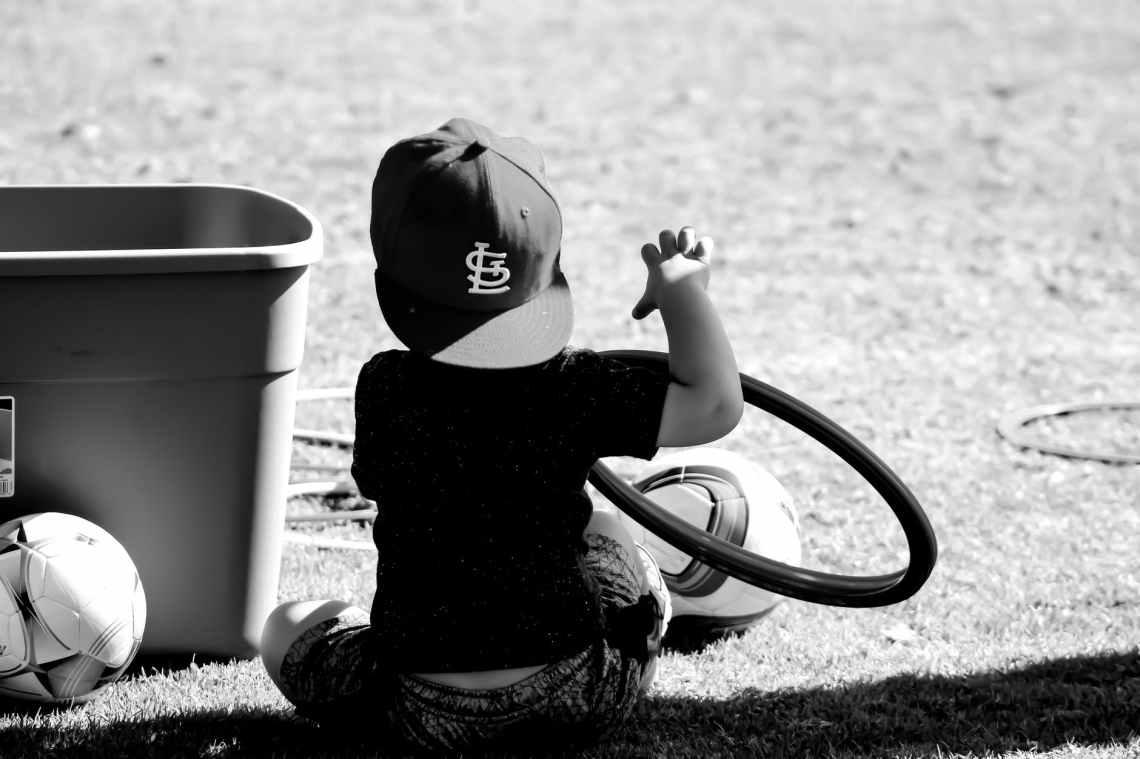 grayscale photo of boy wearing st louis cap