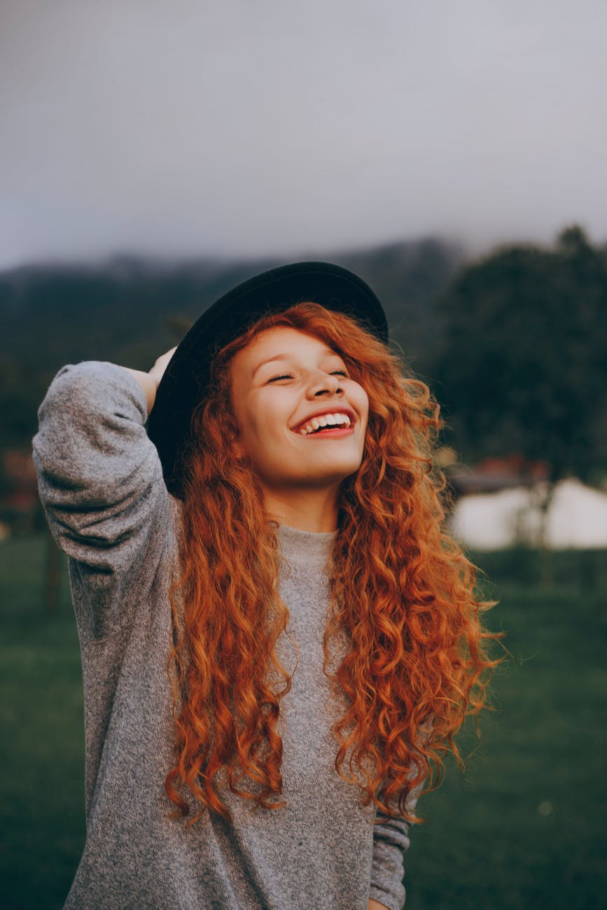 woman holding her hat while smiling