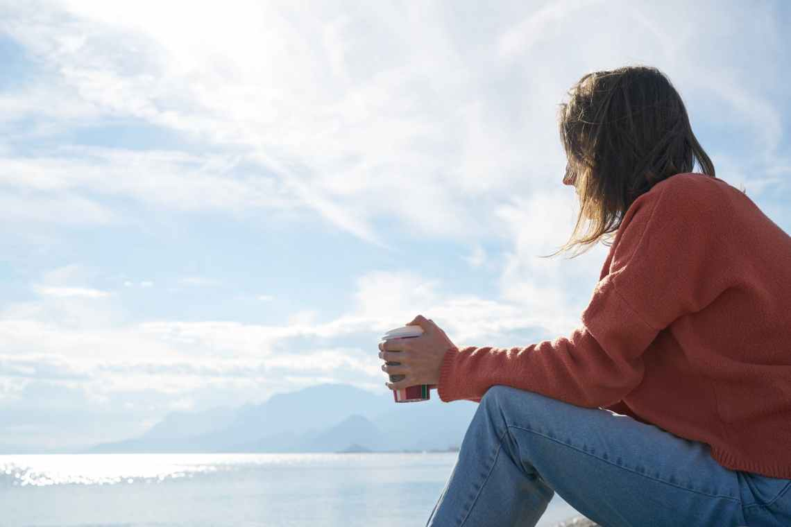 woman sitting in front of body of water