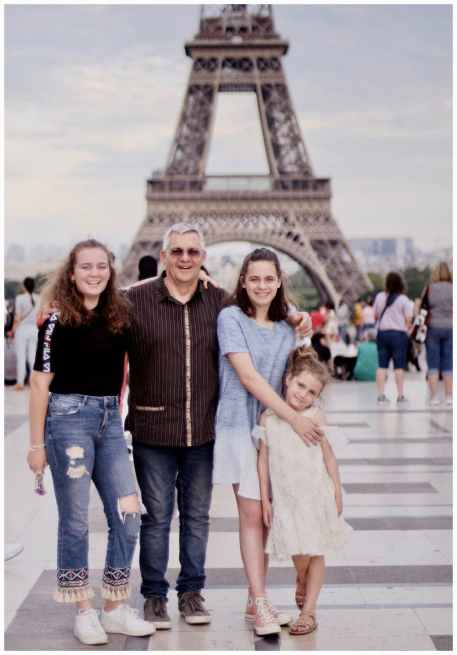 family taking photo near eiffel tower