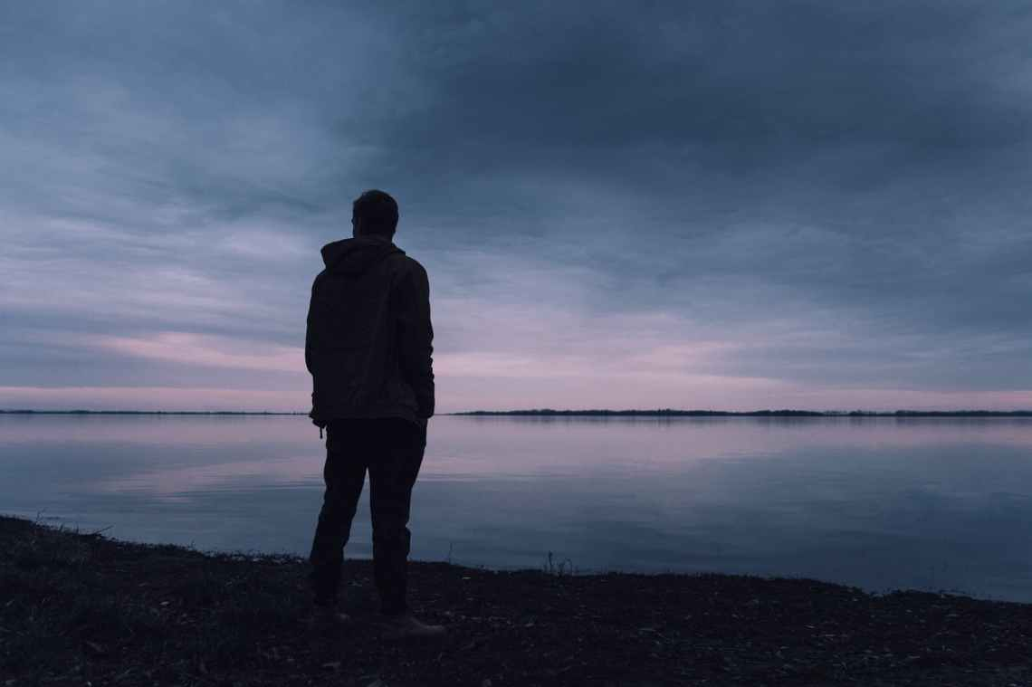 person standing near lake