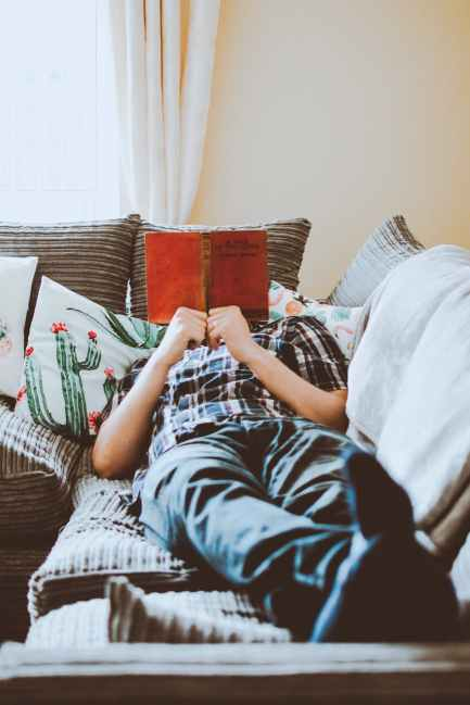 photo of man lying on bed while reading book
