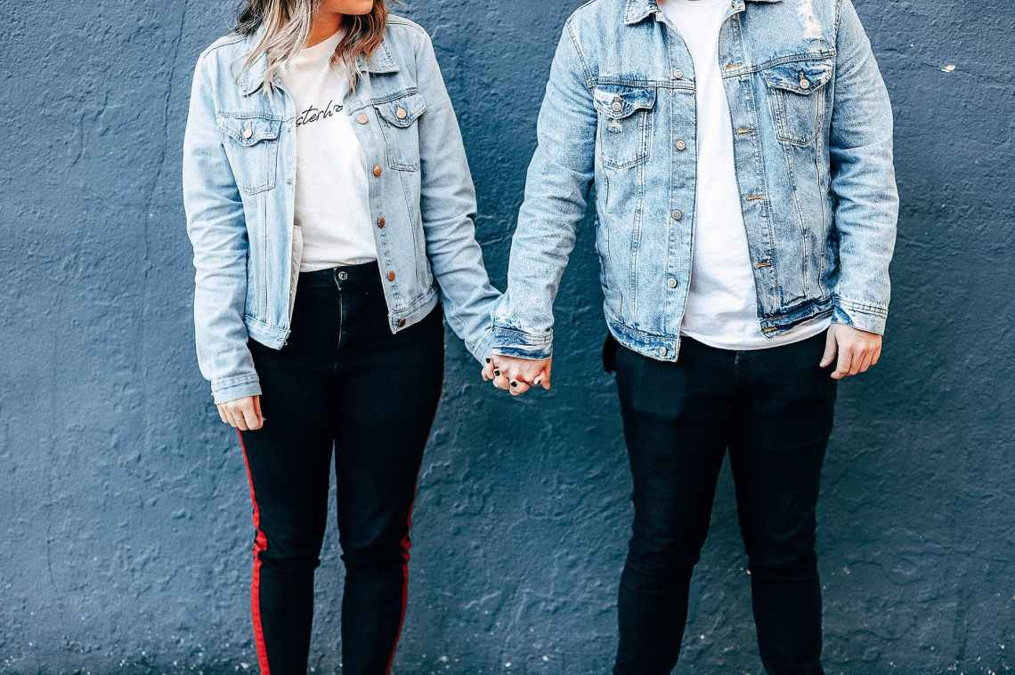two person standing and holding their hands beside blue wall