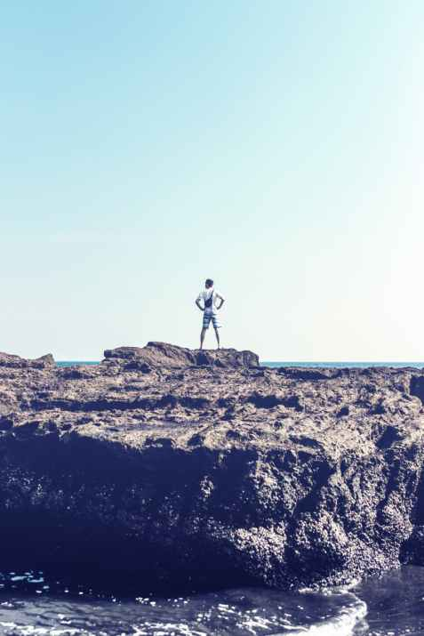 man standing on grey rock